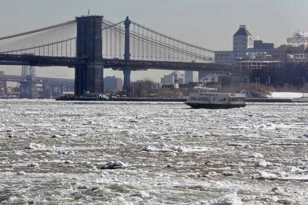 A New York Waterway ferry navigates through ice on the East River near the Brooklyn Bridge, Tuesday, Feb. 24, 2015, in New York. A wide swath of the country is experiencing record-breaking temperatures while other areas are expecting more winter precipitation Tuesday. (AP Photo/Richard Drew) ORG XMIT: NYRD105 Photo: Richard Drew, AP / AP