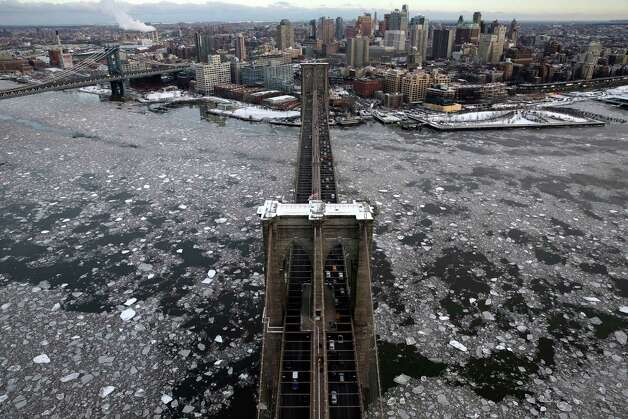 With a view of Brooklyn in the background, ice surrounds the Brooklyn Bridge, Tuesday, Feb. 24, 2015, in New York. A wide swath of the country is experiencing record-breaking temperatures while other areas are expecting more winter precipitation Tuesday. (AP Photo/Seth Wenig) ORG XMIT: NYSW104 Photo: Seth Wenig, AP / AP