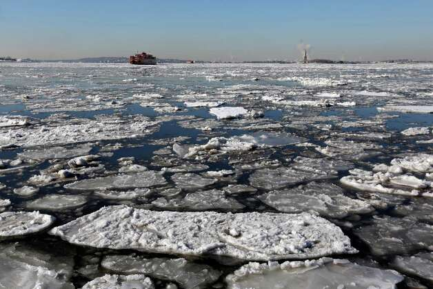 A Staten Island Ferry boat navigates through ice in New York harbor, Tuesday, Feb. 24, 2015. A wide swath of the country is experiencing record-breaking temperatures while other areas are expecting more winter precipitation Tuesday. (AP Photo/Richard Drew) ORG XMIT: NYRD101 Photo: Richard Drew, AP / AP