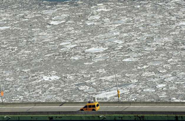 TOPSHOTS A New York City Taxi drives up the FDR Drive alongside and ice filled East River in New York February 24, 2015. Heavy ice in the East River shut down commuter ferry service on Tuesday morning stopping travel between Manhattan, Queens, and Brooklyn.  AFP PHOTO /  TIMOTHY  A. CLARYTIMOTHY A. CLARY/AFP/Getty Images Photo: TIMOTHY A. CLARY, Getty / AFP