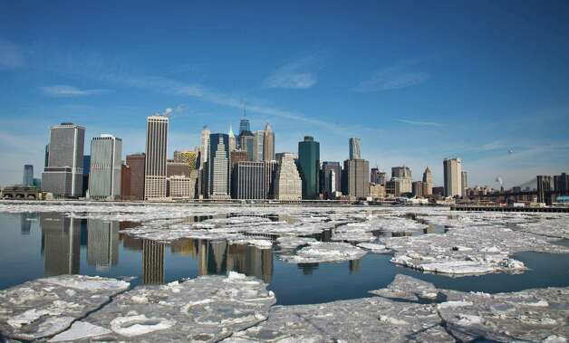 Manhattan's skyline forms the horizon as ice breaks apart flowing along Brooklyn's East River waterfront, Tuesday, Feb. 24, 2015, in New York.  Forecast calls for highs around 20 degrees, with lows down into the teens. Temperatures will be below freezing today and could reach below zero with the windchill, according to the National Weather Service.  (AP Photo/Bebeto Matthews) ORG XMIT: NYBM101 Photo: Bebeto Matthews, AP / AP