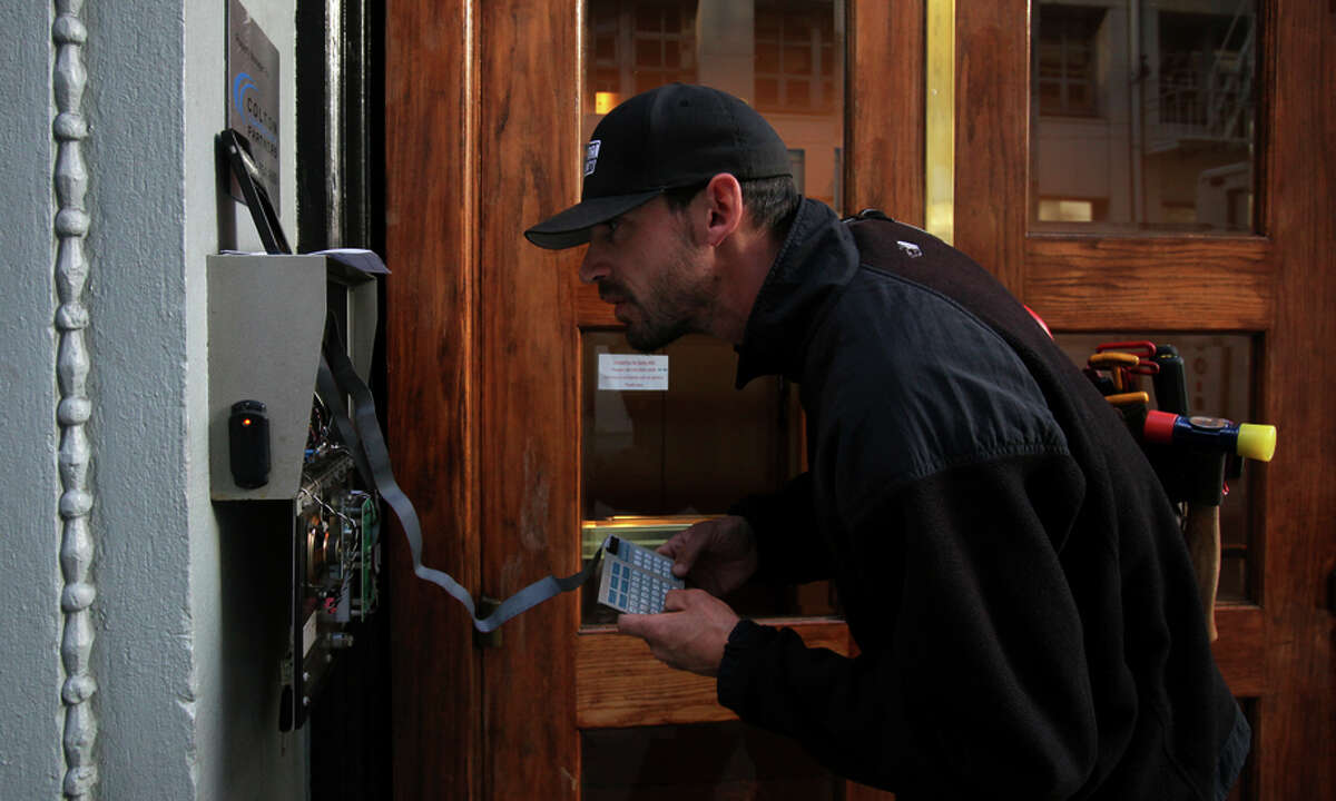 Jon Ahlf, a Warman Security technician, updates a building's security system to handle the new 628 area code.