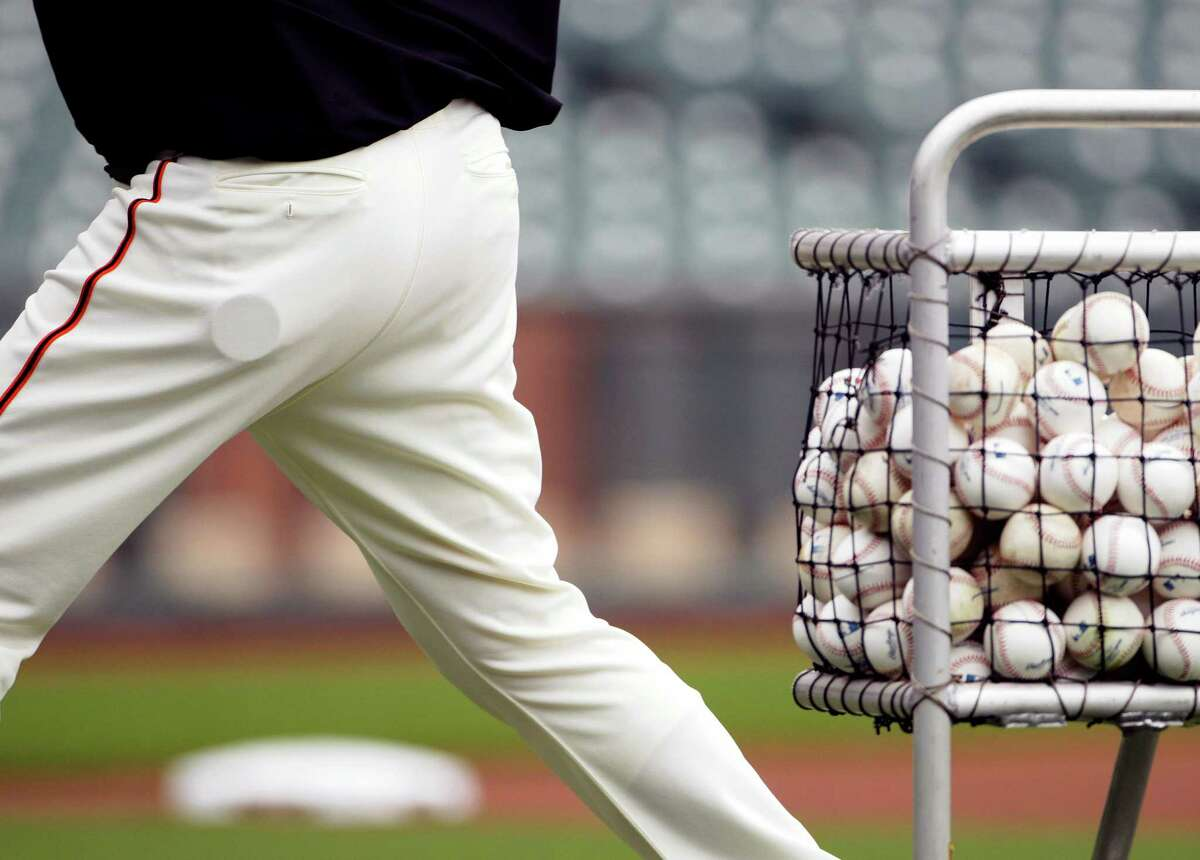 A tin of non-tobacco dip in the pocket of San Francisco Giants bullpen catcher Bill Hayes as he throws during batting practice before a game at AT&T Park against the Philadelphia Phillies.