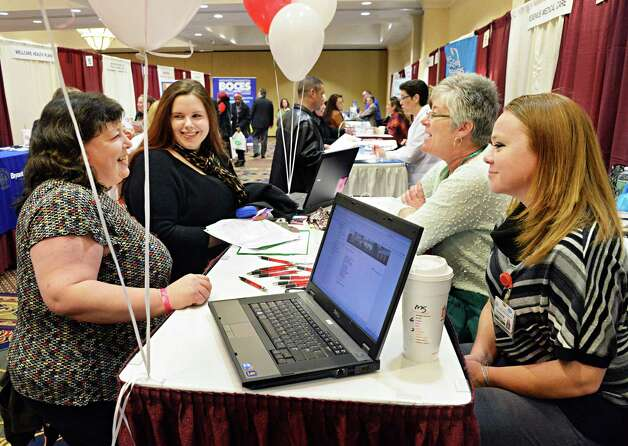 Lori Mallman, left, and Jordan Grignon, both of Albany, speak with Eddy Village Green at Cohoes recruiters Alyson Kelly and Christine Whitaker, right during the Times Union's job fair focusing on health careers at the Albany Marriott hotel Wednesday Feb. 25, 2015, in Colonie, NY.  (John Carl D'Annibale / Times Union) Photo: John Carl D'Annibale / 00030753A