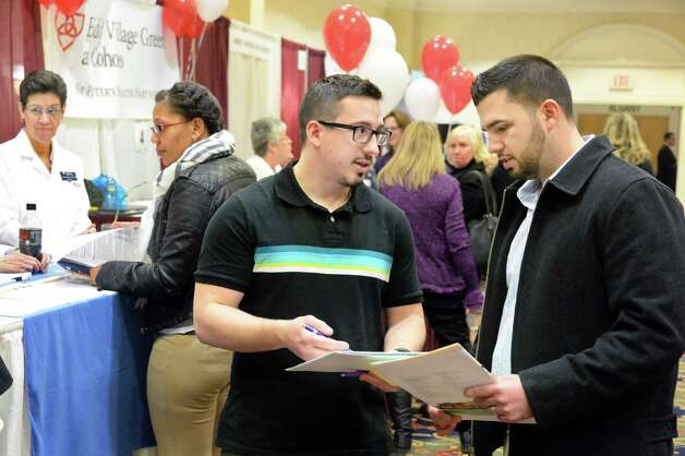 Bob LeMay, left, of Pattersonville, and James Van Buren of Colonie, compare notes during the Times Union's job fair focusing on health careers at the Albany Marriott hotel Wednesday Feb. 25, 2015, in Colonie, NY.  (John Carl D'Annibale / Times Union) Photo: John Carl D'Annibale / 00030753A