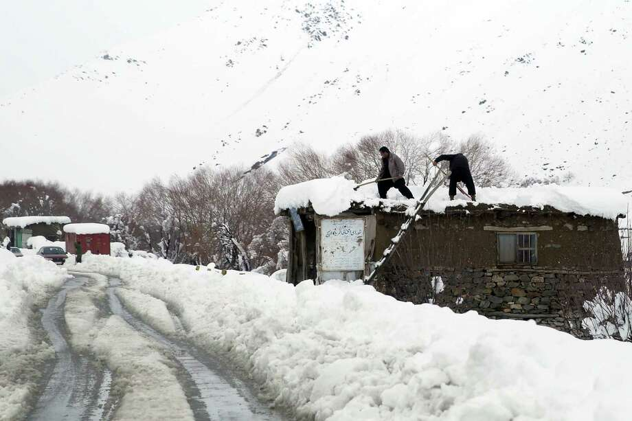 Afghan clean snow from their rooftops in a village close to an avalanche site in Panjshir province north of Kabul. Photo: Massoud Hossaini /Associated Press / AP