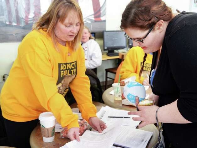 College of Saint Rose adjunct Alyssa Colton, left, hands out information to student Sarah Johnston of Schenectady during an adjuncts protest at the college Wednesday Feb. 25, 2015 in Albany, NY.  (John Carl D'Annibale / Times Union) Photo: John Carl D'Annibale / 00030709A