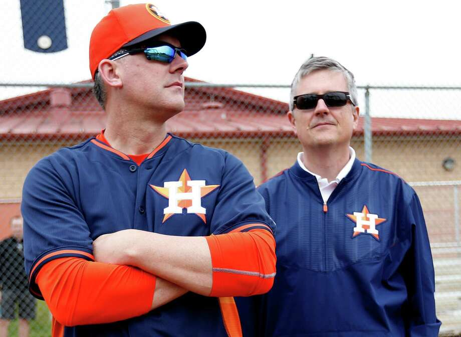 Houston Astros manager A.J. Hinch (left) watches batting practice with Houston Astros general manager Jeff Luhnow during the first full squad workout during spring training at the Osceola County facility on Feb. 25, 2015, in Kissimmee, Fla. Photo: Karen Warren /Houston Chronicle / © 2015 Houston Chronicle