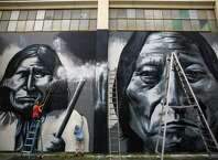 Volunteers scrub and spray off a vandal's paint from images of Geronimo and Sitting Bull after Native American artist Andrew Morrison's murals at Seattle's Wilson-Pacific school building were desecrated. On Wednesday, February 25, 2015, more than a dozen volunteers came together to removed the paint from the artwork. After about four hours the disrespect sprayed on the images was removed.