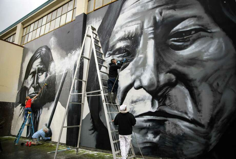 Volunteers scrub and spray off a vandal's paint after Native American artist Andrew Morrison's murals at Seattle's Wilson-Pacific school building were desecrated. On Wednesday, February 25, 2015, more than a dozen volunteers removed the paint from the artwork. Photo: JOSHUA TRUJILLO, SEATTLEPI.COM / SEATTLEPI.COM
