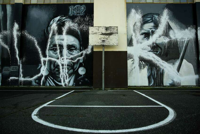 A vandal's paint is shown on images of Chief Joseph and Geronimo after Native American artist Andrew Morrison's murals at Seattle's Wilson-Pacific school building were desecrated. On Wednesday, February 25, 2015, more than a dozen volunteers removed the paint from the artwork.