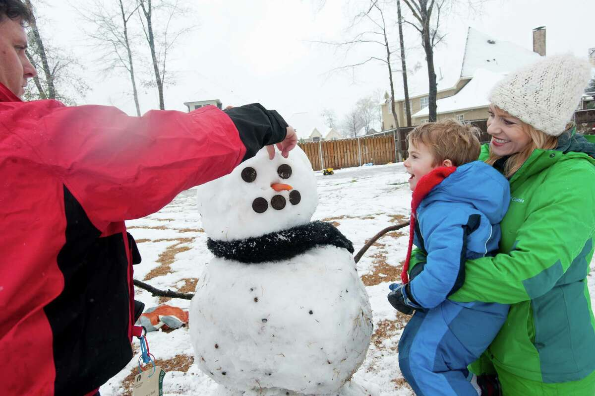 Michael McBride, left, builds a snowman with his son Jackson and wife Brenda in their yard, Wednesday, Feb. 25, 2015, in Tyler, Texas.