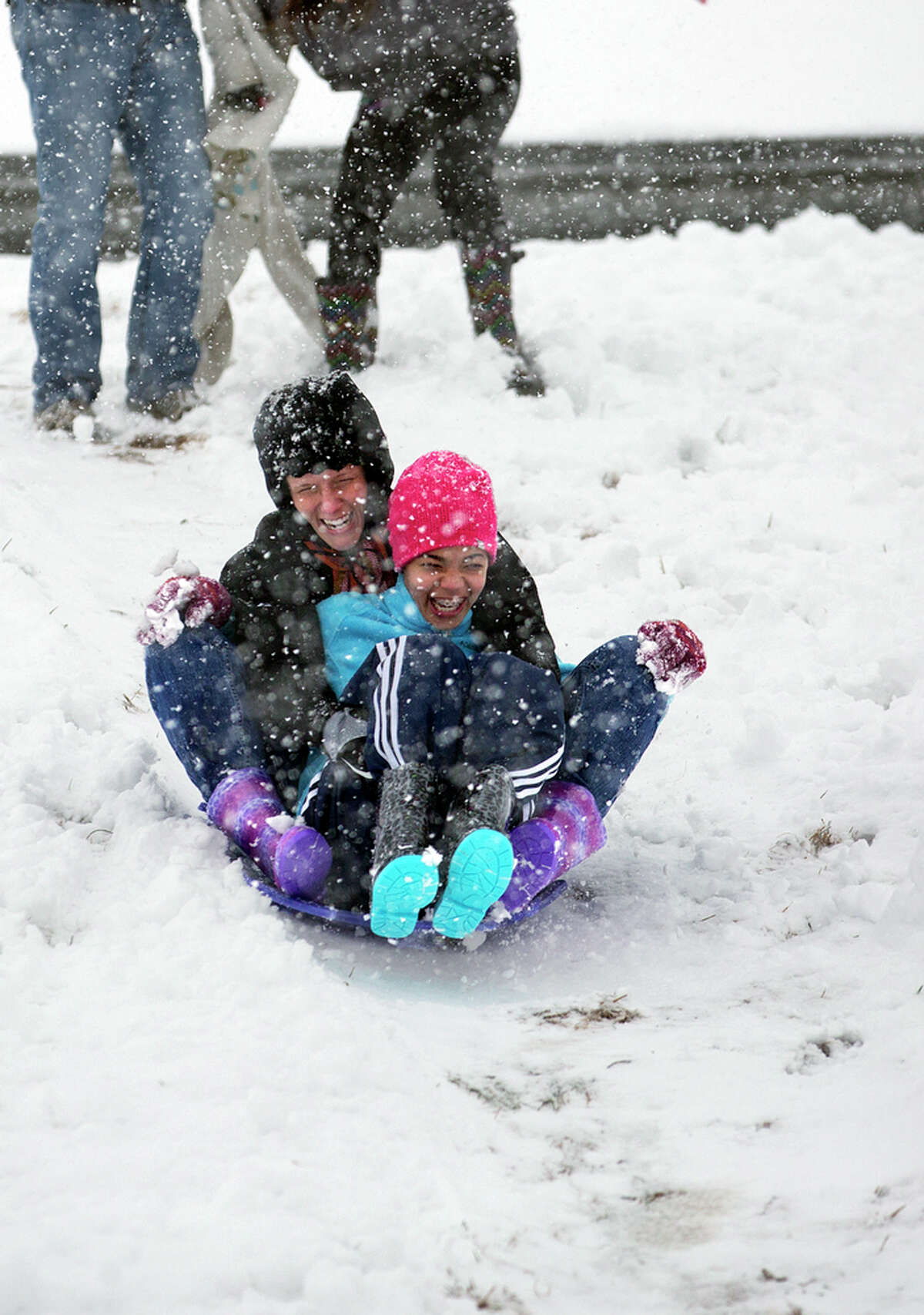 Gabrielle Ard and her mother Lauren slide down the side of the Texas Viaduct as snow falls in Texarkana, Texas, Wednesday, Feb. 25, 2015.