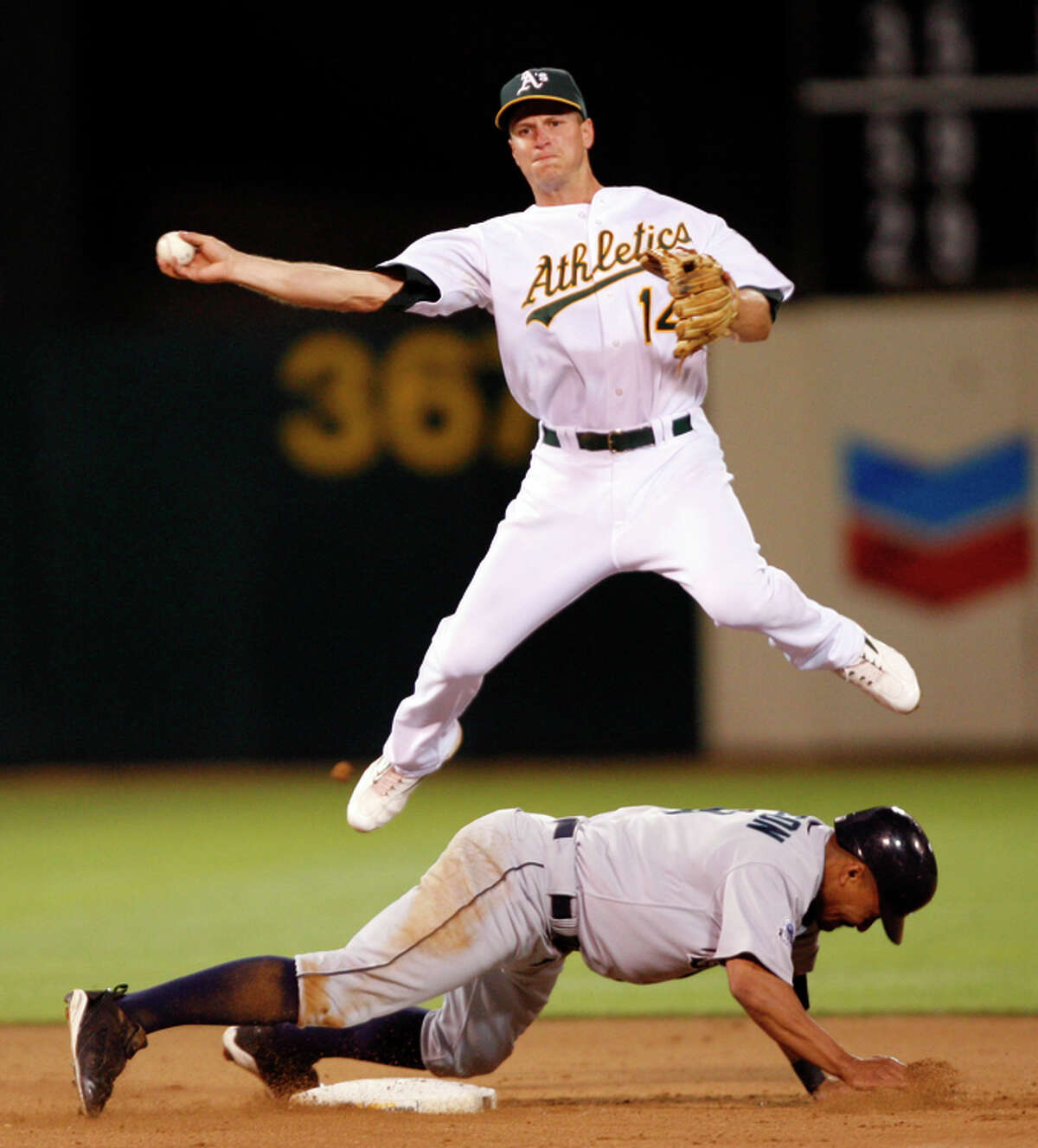 In a home game on July 5, 2007, then-A's second baseman Mark Ellis leaps over the Mariners' Jason Ellison but couldn't get the force out at first base. Ellis twice led the AL in fielding percentage.