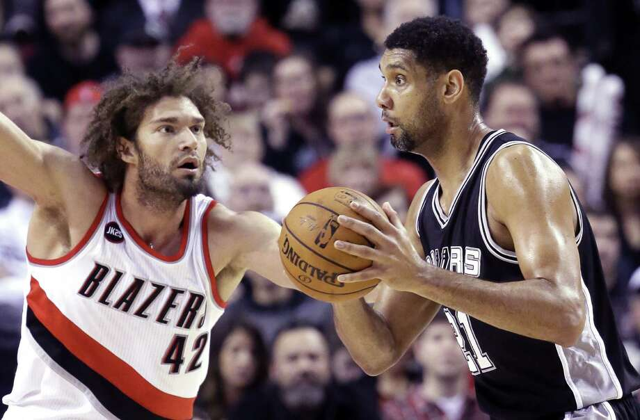 Tim Duncan looks to pass as Portland Trail Blazers center Robin Lopez defends during the first half in Portland, Ore., Wednesday, Feb. 25. The Spurs dropped their fourth straight since the All Star break losing to the Trail Blazers, 111-95. Photo: Don Ryan /Associated Press / AP