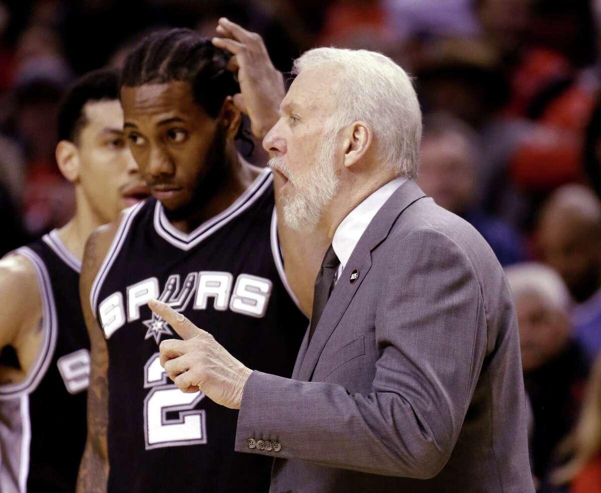 San Antonio Spurs coach Gregg Popovich, right, talks during a break as San Antonio Spurs forward Kawhi Leonard stands at left during the first half of an NBA basketball gam against the Portland Trail Blazers in Portland, Ore., Wednesday, Feb. 25, 2015. (AP Photo/Don Ryan)