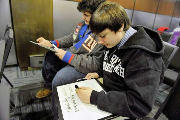 Jason Ambrose, foreground, 15, and Sam Moustafa, 14 both from South Hampton, write anti-smoking messages on white boards to be used in social media at the Empire State Plaza on Wednesday, Feb. 25, 2015, in Albany, N.Y.  Children and tobacco control leaders from around the State gathered at the Capitol to meet with legislators and the general public to stress the importance of funding for tobacco control programs.      (Paul Buckowski / Times Union) Photo: PAUL BUCKOWSKI / 00030746A