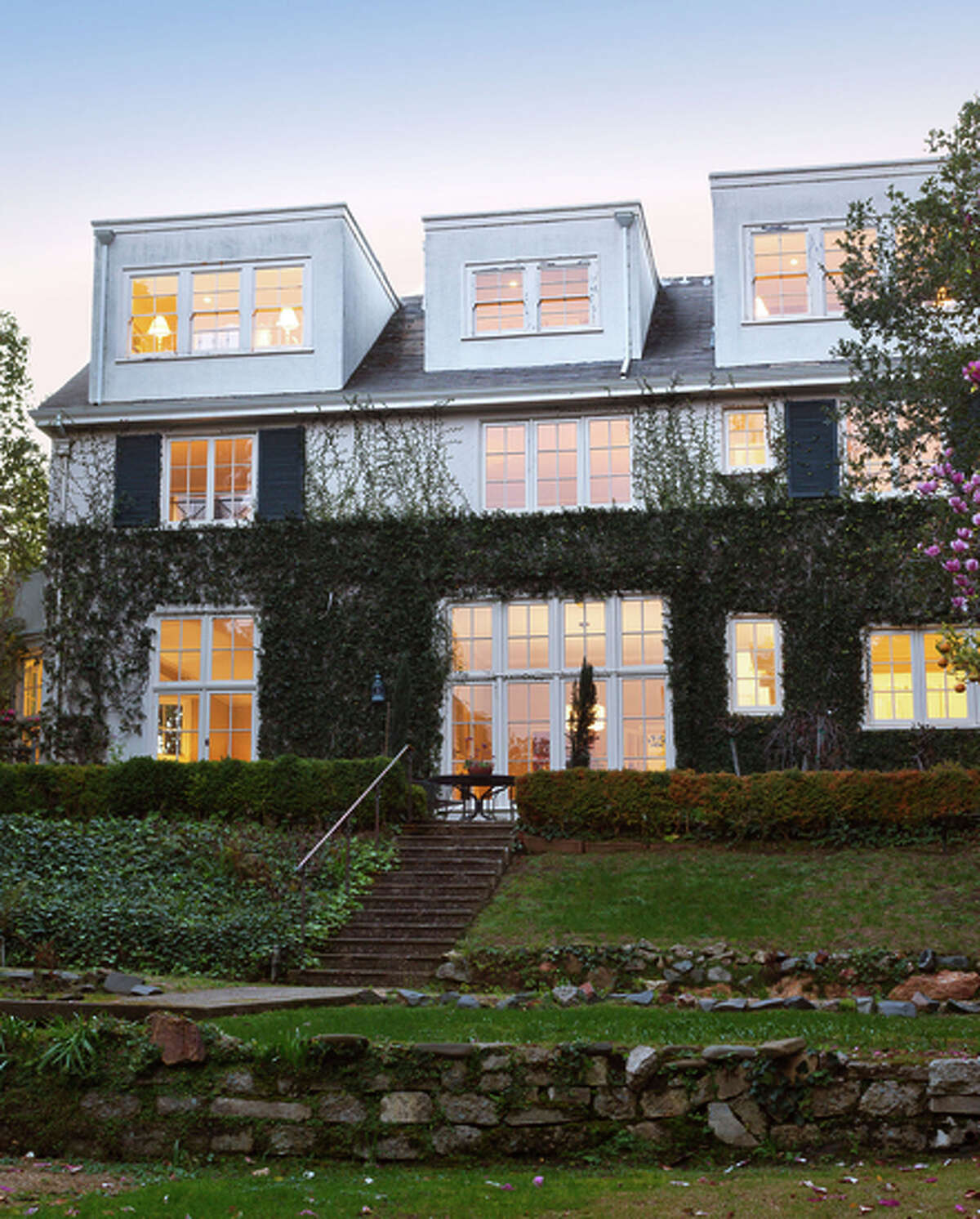 The Piedmont home's plantation shutters and divided light windows are visible from the terraced backyard.