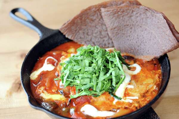 Shakshuka is a traditional Moroccan dish of eggs poached in a spicy, smokey tomato stew served with house-made injera bread on Thursday, Feb. 19, 2015, at The Shop in Troy, N.Y. (Cindy Schultz / Times Union)