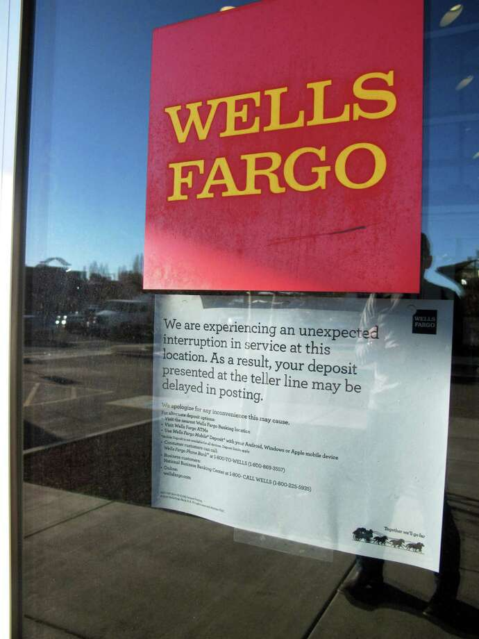 A sign posted on a Wells Fargo branch in Flagstaff warns customers of delays because of the outage. Photo: Felicia Fonseca / Associated Press / AP