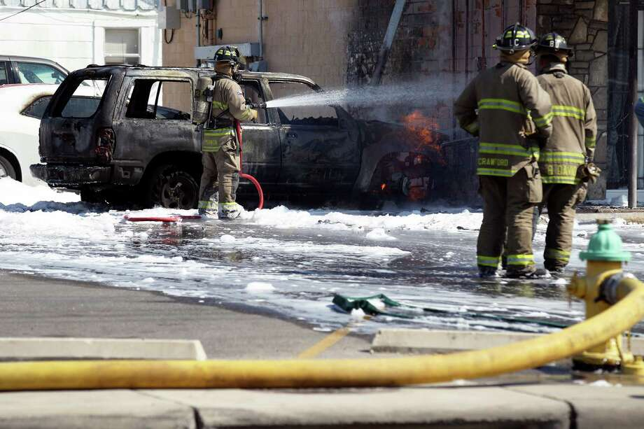 Firefighters spray down a building and and a vehicle after it smashed a gas meter igniting the fire on Thursday afternoon. The building which is part of a commercial structure at the intersection of East Mayfield and Pleasanton roads on the city's South side. Photo: Kin Man Hui