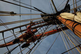 Conor McGowan, top, climbs down from the top of a mast on the tall ship Hawaiian Chieftain, which is offering tours and sailing trips while visiting the bay.