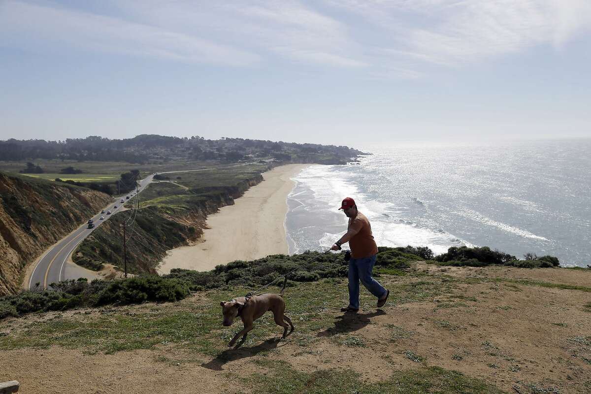 Jack Coons, right, takes his dog Cooper on a training walk on a bluff at McNee Ranch State Park, Wednesday, Feb. 25, 2015, in Montara, Calif. (AP Photo/Marcio Jose Sanchez)