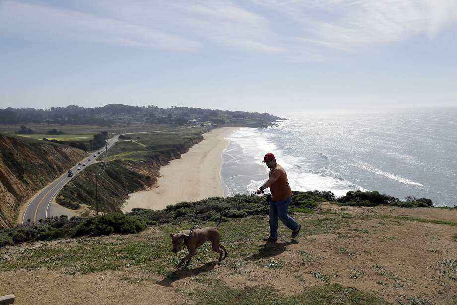 Jack Coons, right, takes his dog Cooper on a training walk on a bluff at McNee Ranch State Park, Wednesday, Feb. 25, 2015, in Montara, Calif. (AP Photo/Marcio Jose Sanchez) Photo: Marcio Jose Sanchez, Associated Press