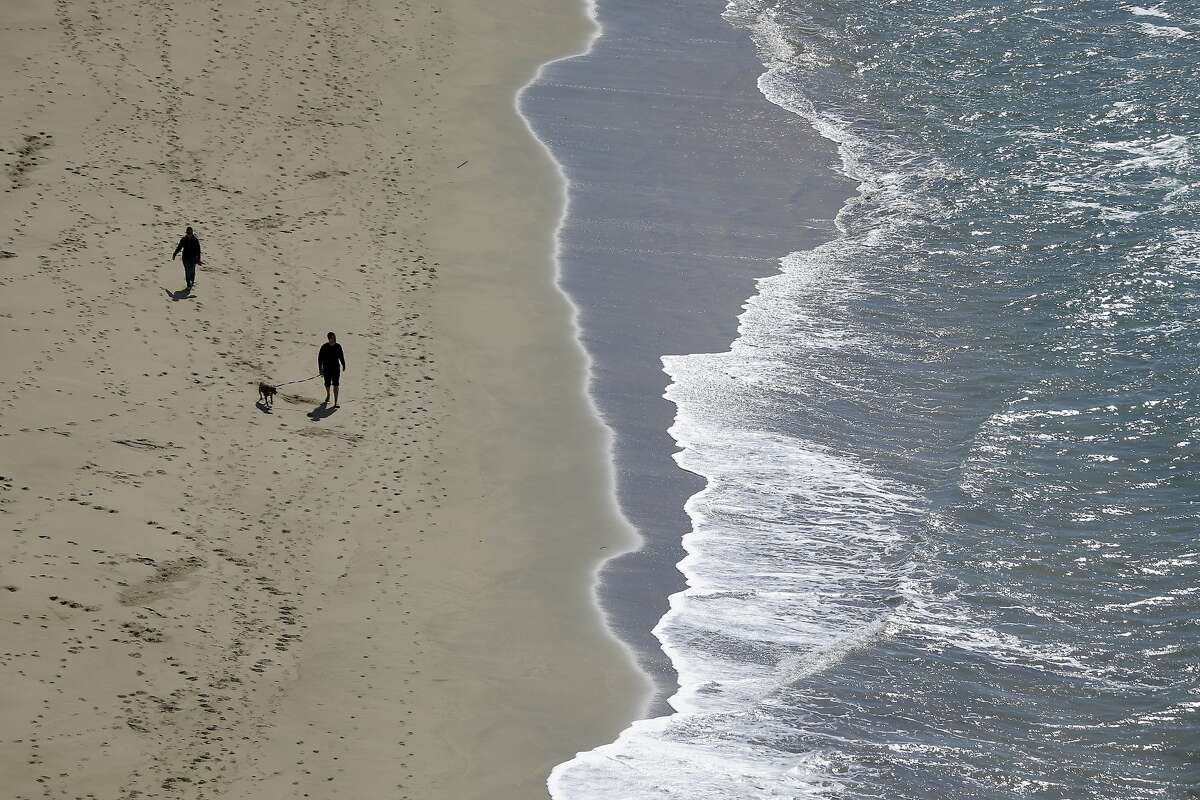 Visitors walk along the shore at Montara State Beach, Wednesday, Feb. 25, 2015, in Montara, Calif. (AP Photo/Marcio Jose Sanchez)