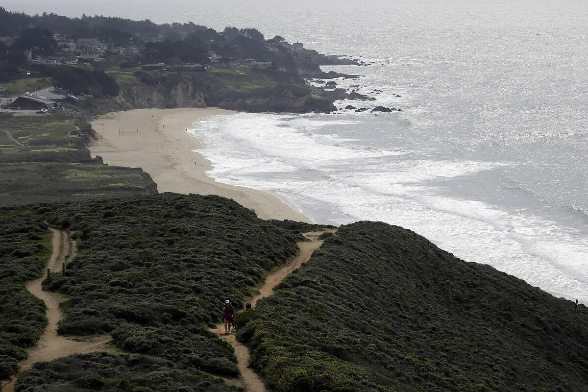 A visitor walks on a trail at McNee Ranch State Park with Montara State Beach as a backdrop, Wednesday, Feb. 25, 2015, in Montara, Calif. (AP Photo/Marcio Jose Sanchez)