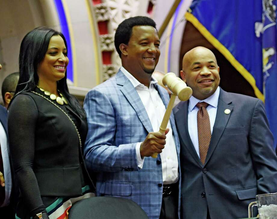 Assembly Speaker Carl Heastie, right, hands over the gavel to baseball great Pedro Martinez and his wife Carolina on the Speaker's podium Thursday afternoon Feb. 26, 2015, in the  Assembly Chamber in Albany, N.Y.  Martinez will be inducted in to the Baseball Hall of Fame this summer.   (Skip Dickstein/Times Union) Photo: SKIP DICKSTEIN / 00030758A