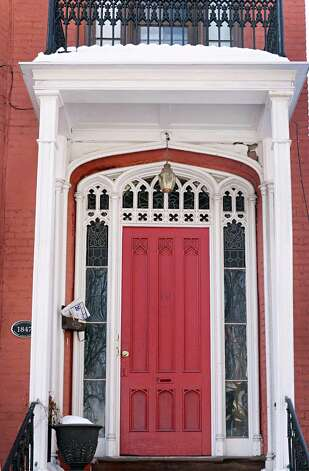 The elaborate panel door flanked by windows with pointed arches at this 10 Madison Place rowhouse is a good example of an entryway found in Gothic Revival style.  (John Carl D'Annibale / Times Union) Photo: John Carl D'Annibale / 00030728D