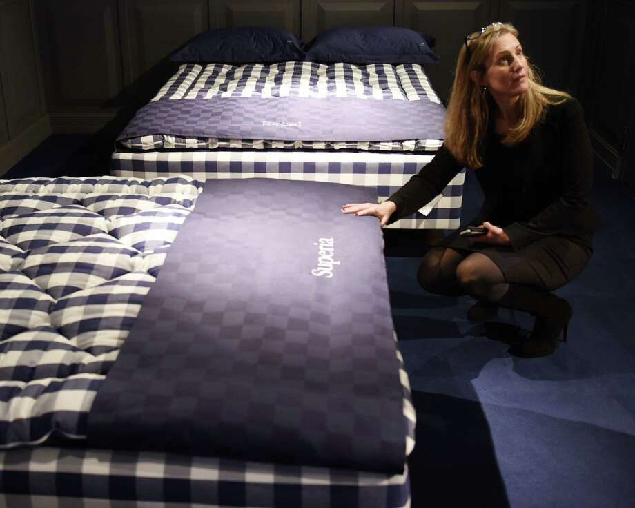 Showroom manager Lori DeRocco shows different bed options at Hästens in Greenwich, Conn. Thursday, Feb. 26, 2015.  The high-end Swedish bed retailer added a new store in Greenwich in October and held its opening party Thursday night.  Beds at Hästens, a fifth-generation family brand since 1852, can go for more than $100,000. Photo: Tyler Sizemore / Greenwich Time