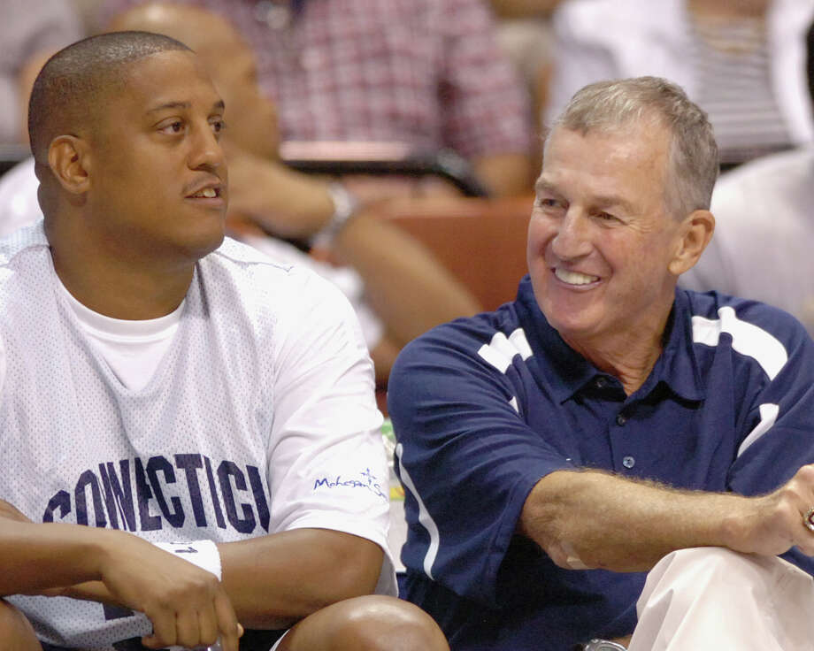 Connecticut head basketball coach Jim Calhoun, center, shares a smile with former players Tate George, left, and Caron Butler During the Jim Calhoun Celebrity Classic basketball game at the Mohegan Sun Arena in Uncasville, Conn., on Saturday Aug. 8, 2008. George has been indicted on federal fraud charges for his role in a $2 million investment scheme.  (AP Photo/Fred Beckham) Photo: Fred Beckham, ASSOCIATED PRESS / Associated Press