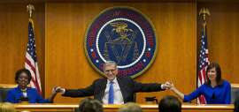 FCC chairman Tom Wheeler joins hands with fellow commissioners Mignon Clyburn, left, and Jessica Rosenworcel in cheering the seething bitterness they are about to inflict in the dark and scary heart of Mitch McConnell. And Comcast. And Verizon. Et al.