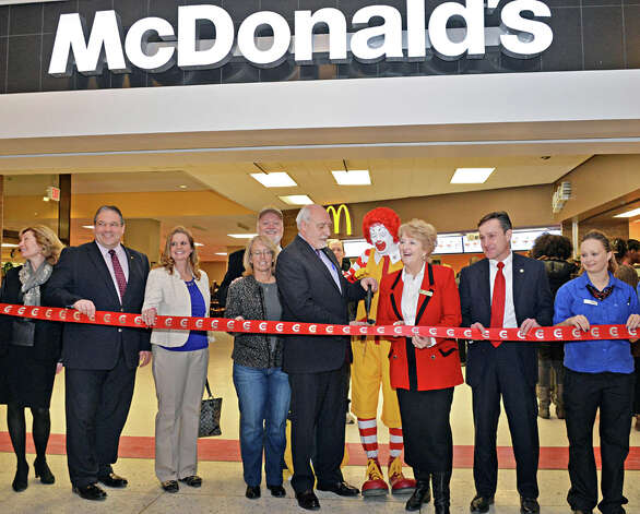 McDonald's Owner/Operators John and Kathie Reeher, center, are joined by McDonald's ambassador of fun, Ronald McDonald and dignitaries in cutting a ribbon to celebrate the grand re-opening of McDonald's at Empire State Plaza Celebrates Thursday, Feb. 26, 2015, in Albany, NY.  (John Carl D'Annibale / Times Union) Photo: John Carl D'Annibale, Albany Times Union / 00030726A