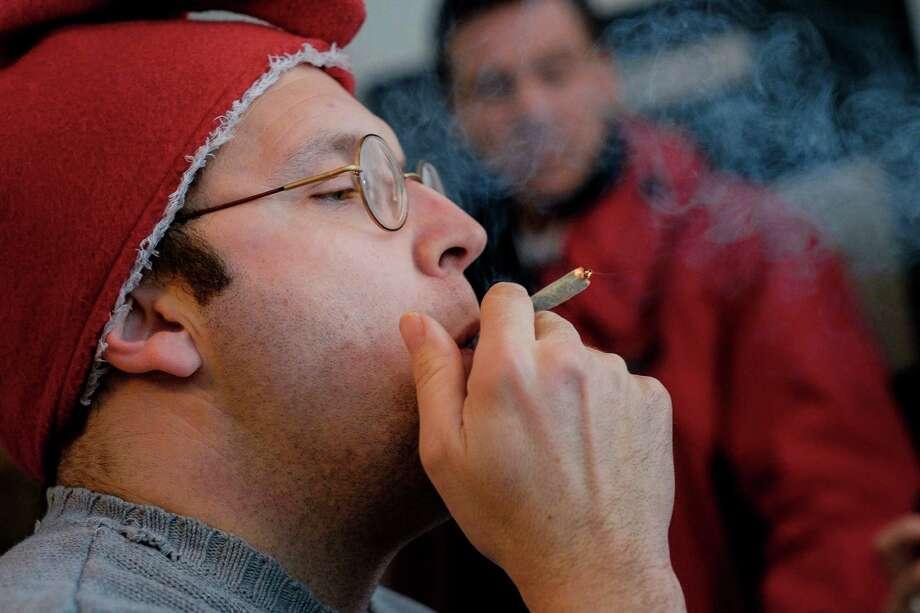 Adam Eidinger, chairman of the DC Cannabis Campaign, smokes a joint Thursday at a news conference about marijuana decriminalization. Photo: T.J. KIRKPATRICK, STR / NYTNS