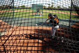 San Francisco Giants' Brandon Belt takes a cut in a batting cage in Scottsdale, Ariz., on Wednesday.
