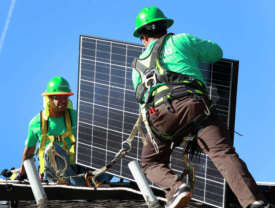 PALO ALTO, CA - MARCH 31: Lead installers for SolarCity Charles Groves (R) and Matt Parra (L) install solar electrical panels on the roof of a home on Thursday, March, 31, 2011 in Palo Alto, California, (Photo by Tony Avelar / The Christian Science Monitor via Getty Images) Photo: Christian Science Monitor / Christian Science Monitor/Getty / ONLINE_CHECK