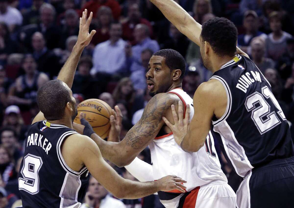 Portland Trail Blazers forward LaMarcus Aldridge, middle, is double teamed by the San Antonio Spurs' Tony Parker, left, and Tim Duncan during the first half of an NBA basketball game in Portland, Ore., Wednesday, Feb. 25, 2015. (AP Photo/Don Ryan)