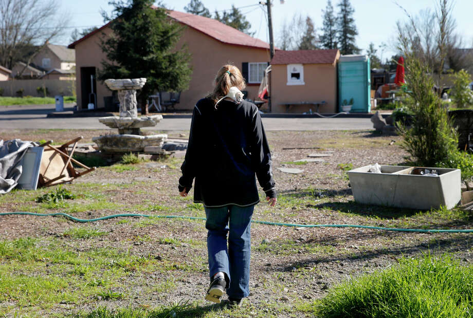 A woman named Dee, the girlfriend of Guillermo Avina, one of the men arrested, walks with her pet rat on the compound where a woman allegedly was held. Photo: Brant Ward / The Chronicle / ONLINE_YES