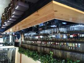 A view of the long wood-topped bar at Sunset Reservoir Brewing Company.