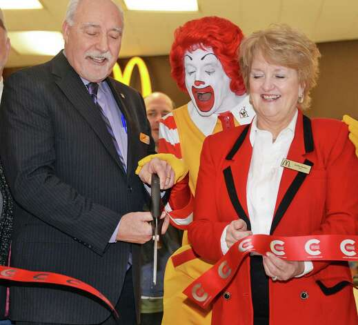 McDonald's Owner/Operators John and Kathie Reeher are joined by McDonald's ambassador of fun, Ronald McDonald, in cutting a ribbon to celebrate the grand re-opening of McDonald's at Empire State Plaza Celebrates Thursday, Feb. 26, 2015, in Albany, N.Y.  (John Carl D'Annibale / Times Union) Photo: John Carl D'Annibale / 00030726A