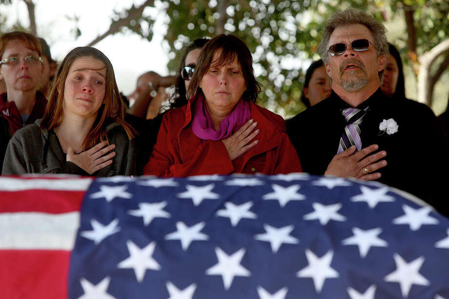 Ashley Weyrick, the sister of Amanda Lee Weyrick, and their parents, Patricia and Randy Weyrick, stand for the gun salute and playing of Taps at Fort Sam Houston National Cemetery in San Antonio on Thursday, Feb. 26, 2015. Photo: Lisa Krantz, San Antonio Express-News / San Antonio Express-News