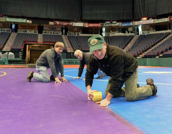 State wrestling committee members, from left; Gene Tracy, Fred Brown and Dick Meldrim test mats for safety before final taping during set up for the state wrestling championships  Thursday Feb. 26, 2015, at the Times Union Center in Albany, NY. Event runs Friday and Saturday.  (John Carl D'Annibale / Times Union) Photo: John Carl D'Annibale / 00030774A