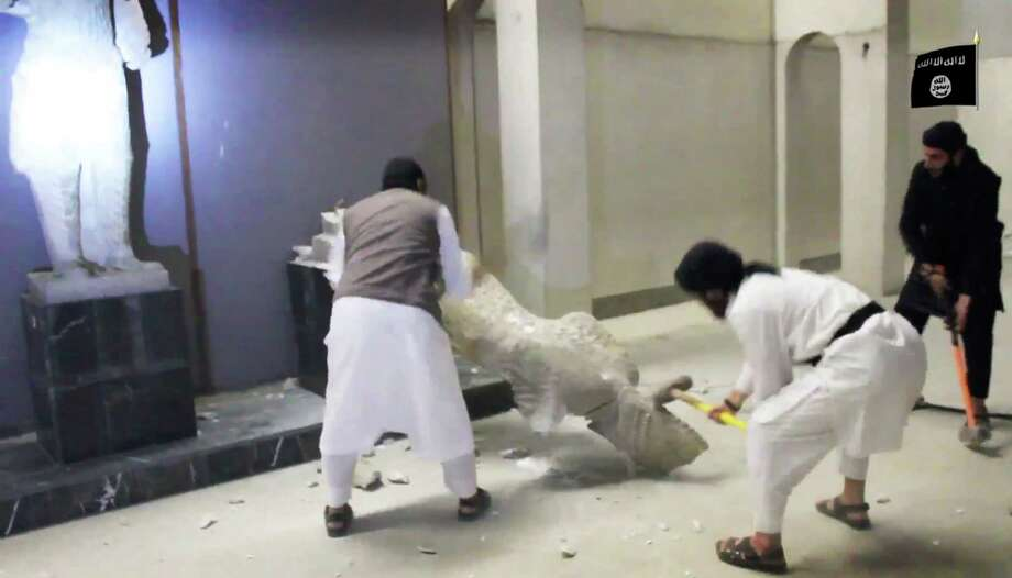 ISIS   militants take sledge hammers to an ancient artifact in the Ninevah Museum in Mosul, Iraq. The group has destroyed a number of shrines — including Muslim holy sites — in order to eliminate what it views as heresy. Photo: Associated Press / Militant Video
