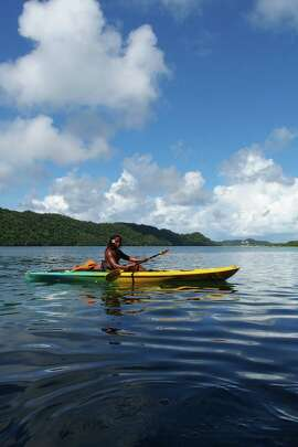 Fonzie, a guide with Sam's Tours in Koror, takes a moment to enjoy the scenery during a kayak tour of Nikko Bay in the Rock Islands area of Palau.