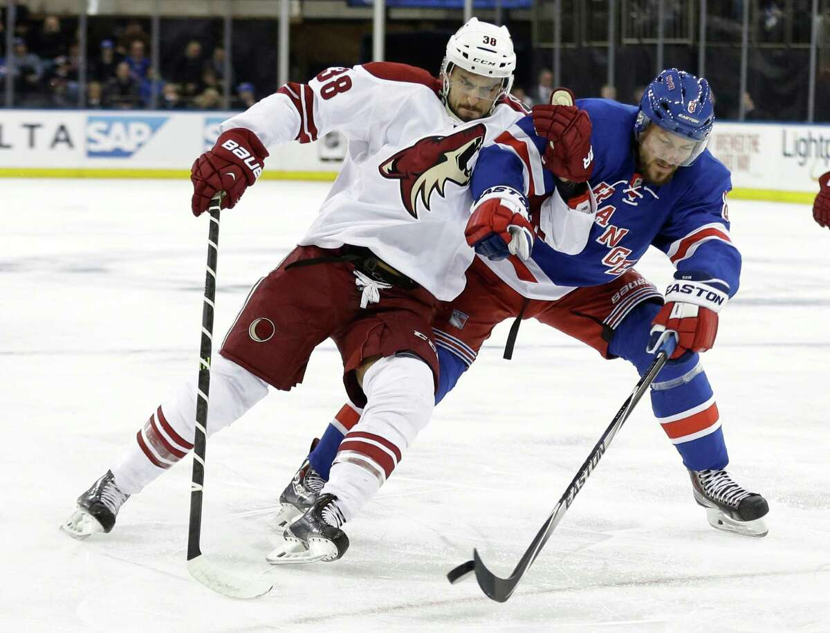 Arizona Coyotes' Lucas Lessio (38) and New York Rangers' Kevin Klein (8) fight for control of the puck during the first period of an NHL hockey game Thursday, Feb. 26, 2015, in New York. (AP Photo/Frank Franklin II) ORG XMIT: MSG104
