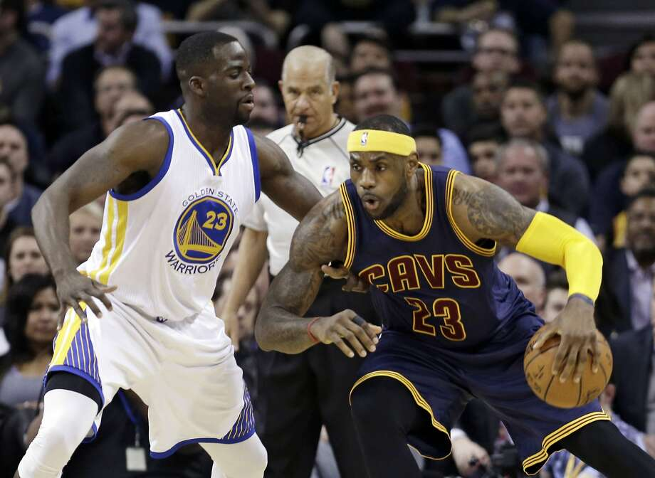 Cavaliers forward LeBron James (right) tries to drive around Warriors forward Draymond Green in a game Feb. 26 in Cleveland. Photo: Tony Dejak, Associated Press