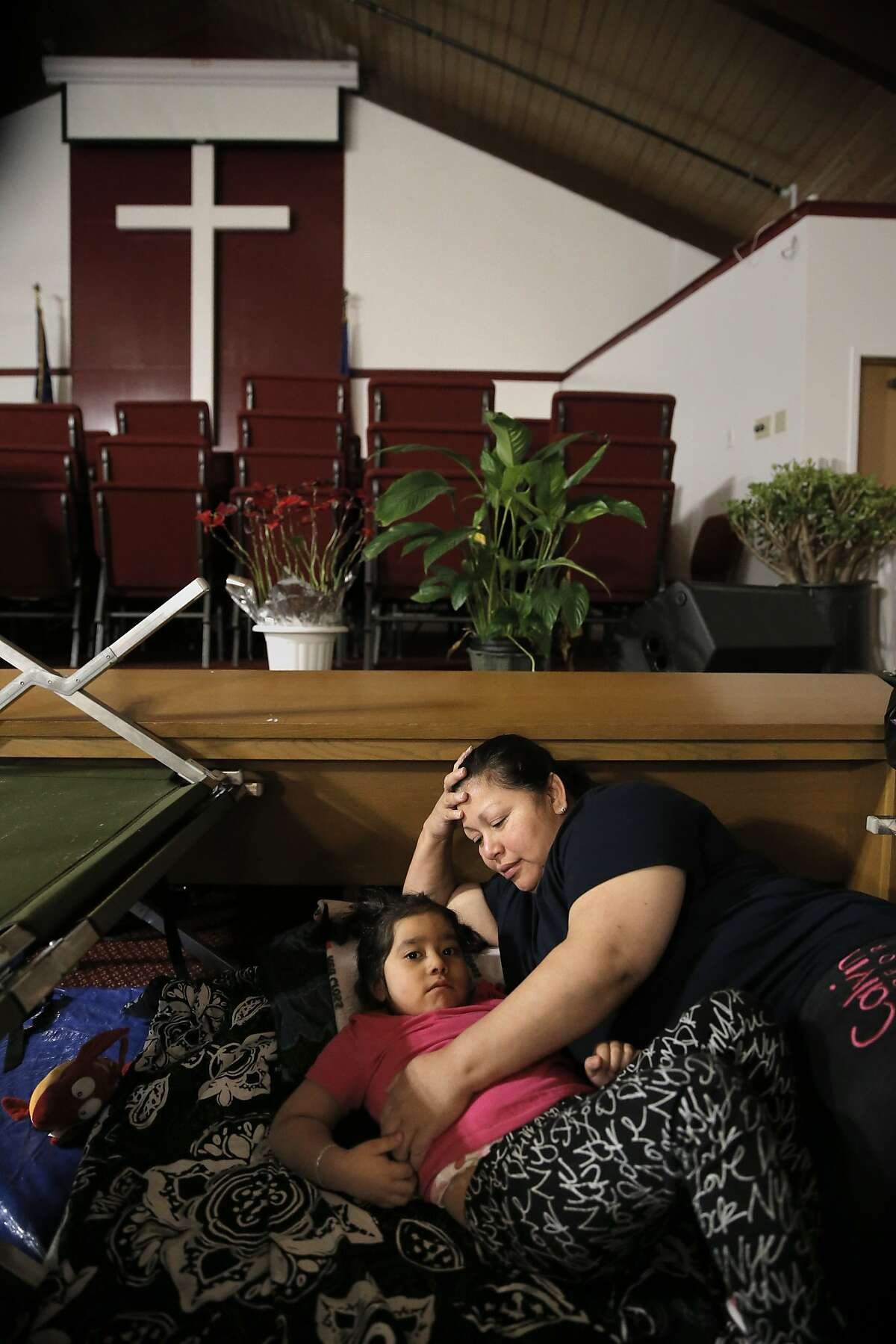 Anna Ortiz and her 5-year-old daughter Arianna inside the Chapel which has been converted for sleeping, at the Salvation Army Mission Corps center where they have been staying after being left homeless following the 22nd St. fire that left dozens of people without a place to live in San Francisco, Calif. as seen on Thurs. February 26, 2015.